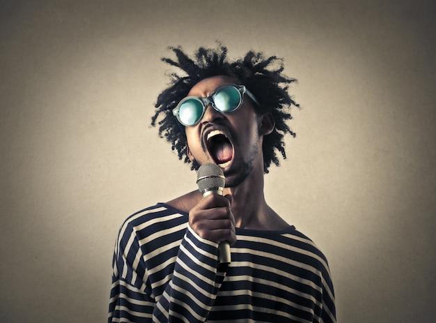 Homem afro gritando em um microfone