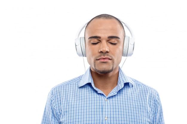 Homem afro relaxado, ouvindo música com seus fones de ouvido isolados
