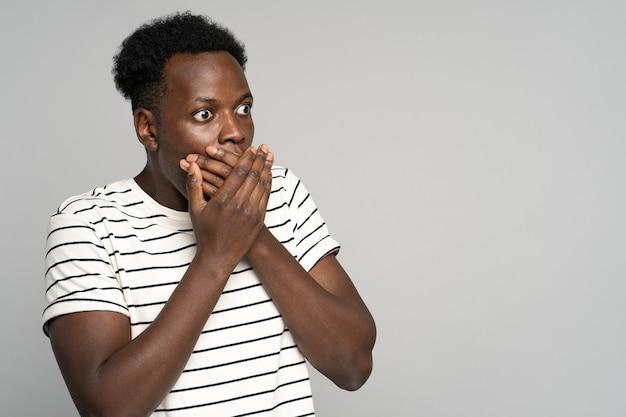 Homem afro surpreso abre grandes olhos, cobre a boca chocada olhando para o espaço da cópia, oferta, venda