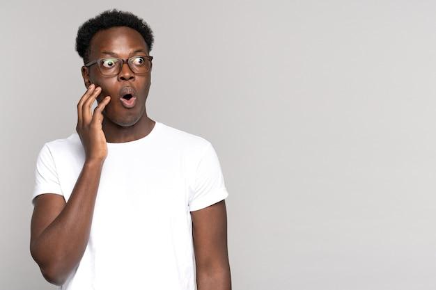 Homem afro surpreso faz com que grandes olhos se abram, tocando seu rosto, chocado com preços inusitadamente baixos