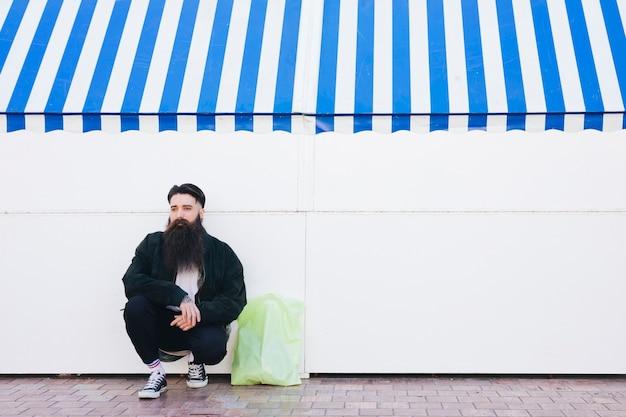 Homem agachado perto da parede com saco de transporte de plástico verde
