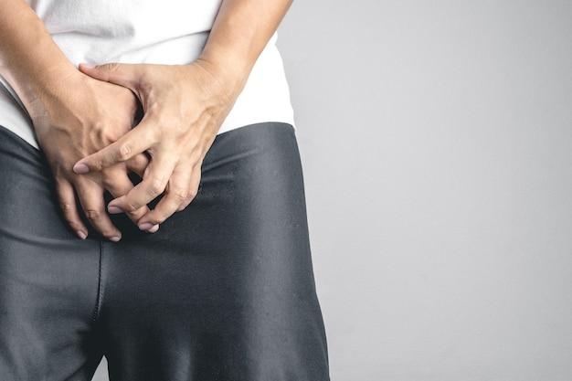 Homem agarrar ou cobrir sua virilha