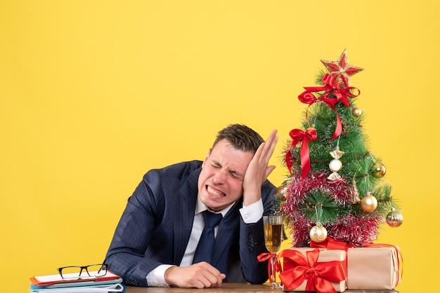 Homem agitado de vista frontal com os olhos fechados sentado à mesa perto da árvore de natal e presentes em fundo amarelo