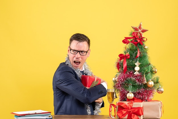 Homem agitado de vista frontal escondendo seu presente sentado à mesa perto da árvore de natal e presentes sobre fundo amarelo