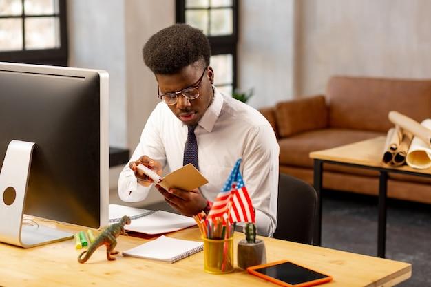 Homem agradável de cabelos escuros segurando seu caderno enquanto lê suas anotações