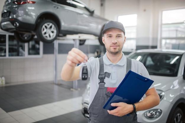 Homem agradável e confiante fica e olha para a câmera. ele segura as chaves do carro e uma pasta plástica com documentos. há atrelados atrás dele.