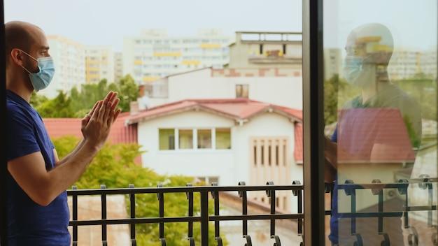 Homem agradecido batendo palmas em apoio aos médicos na varanda de seu apartamento