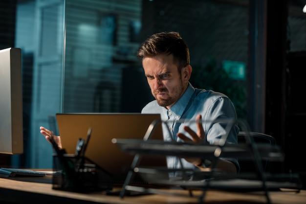Homem agressivo gritando com laptop