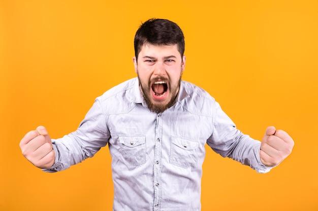 Homem agressivo gritando com os punhos cerrados na parede laranja