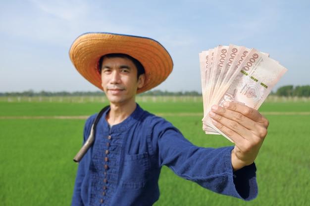 Homem agricultor asiático segurando o dinheiro das notas tailandesas na fazenda de arroz verde. foco da imagem na nota e no rosto desfocado.