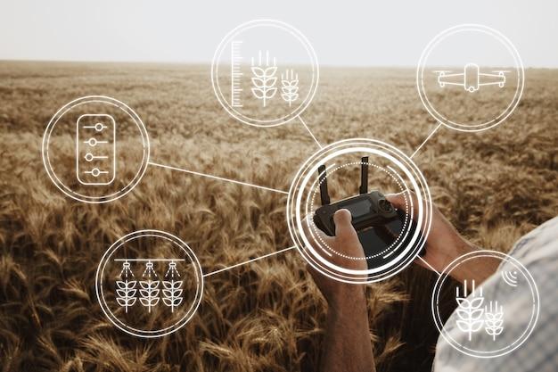 Homem agricultor em pé no campo de trigo e controlando tecnologias de drones no conceito de agricultura