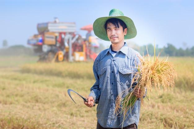 Homem agricultor tailandês feliz segurando arroz de culturas de foice com fundo de carro de colheita na fazenda de campo