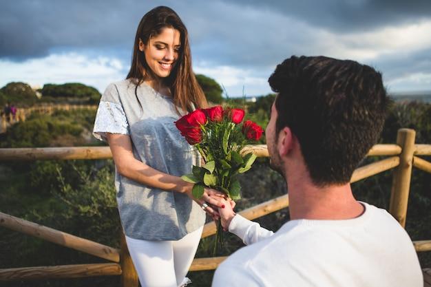 Homem ajoelhado entregar um buquê de rosas para uma mulher