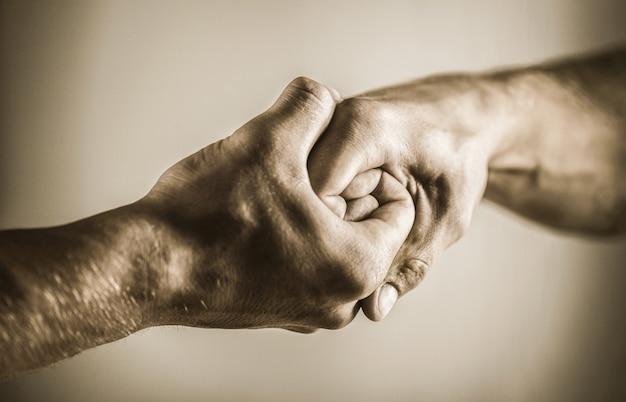 Homem ajuda as mãos, tutela, proteção. aperto de mão amigável, amigos cumprimentando. resgate, mão amiga. mão masculina unida em um aperto de mão. aperto de mão, braços. duas mãos, braço isolado, mão amiga de um amigo