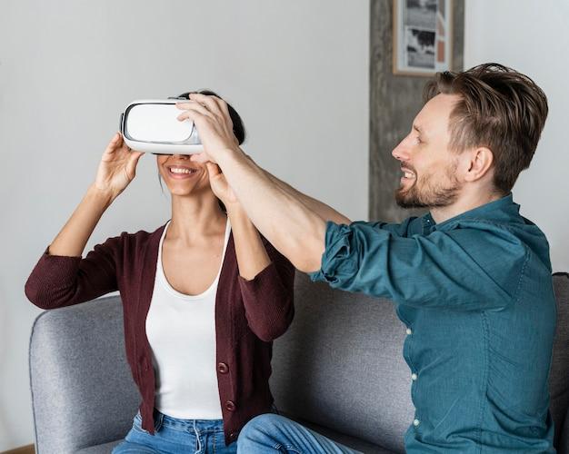 Homem ajudando mulher a colocar um fone de ouvido de realidade virtual
