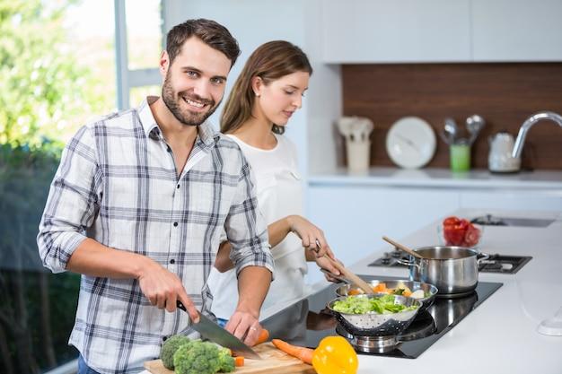 Homem ajudando mulher na preparação de alimentos em casa