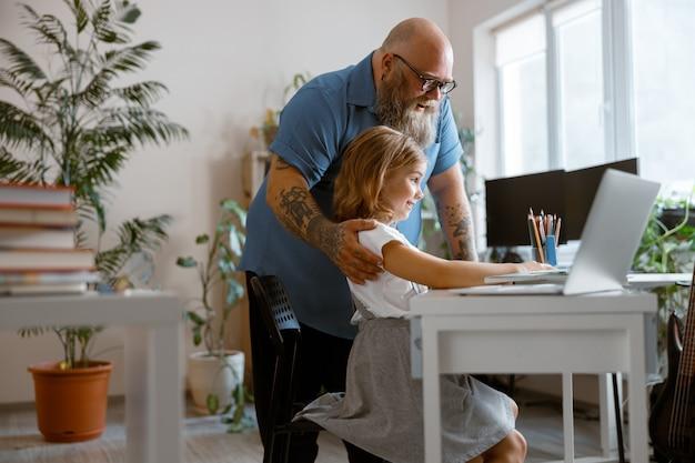 Homem alegre a abraçar a filha fazendo hometask perto do laptop na mesa na sala de luz
