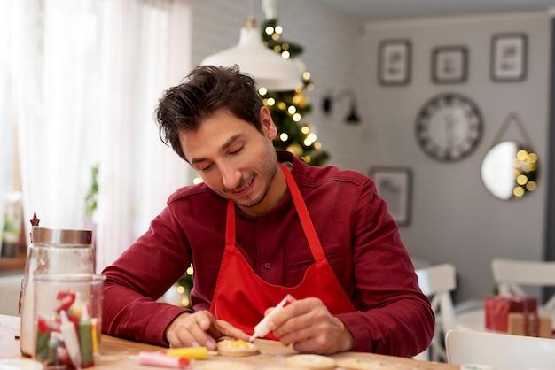 Homem alegre a decorar biscoitos para o natal