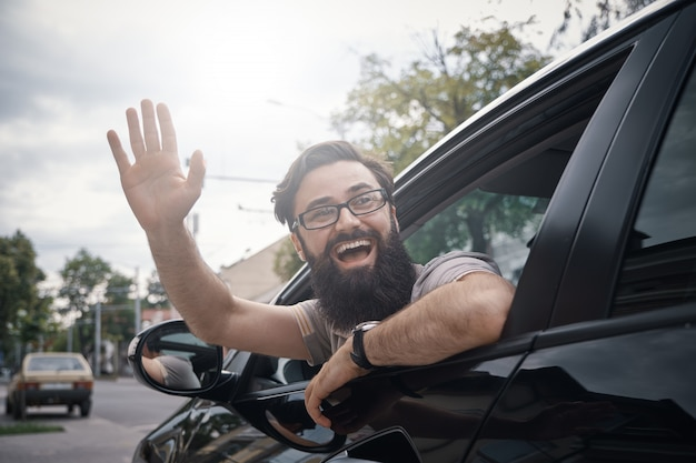 Homem alegre, acenando enquanto dirigia um carro