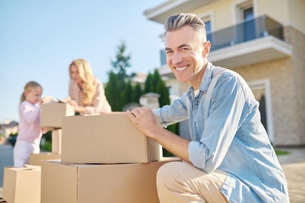 Homem alegre agachado perto de caixas na rua