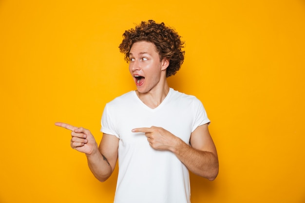 Homem alegre animado com cabelo castanho encaracolado, gesticulando o dedo de lado na copyspace