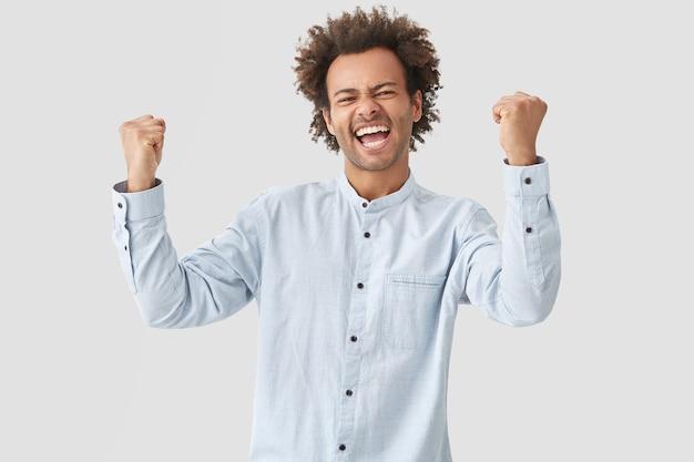 Homem alegre aperta os punhos, tem expressão feliz, grita sim, vestido com roupas brancas