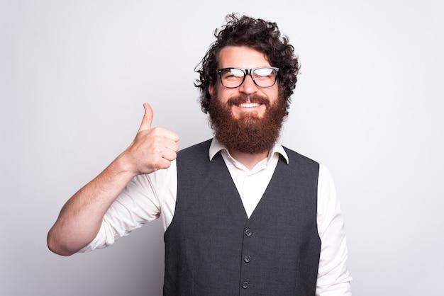 Homem alegre barbudo hippie de terno, parecendo confiante e mostrando o polegar