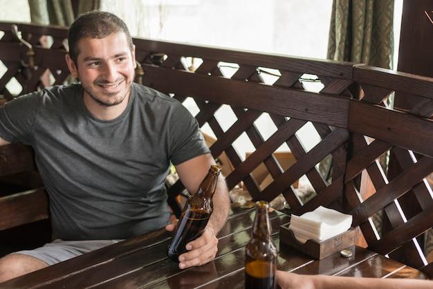 Homem alegre, bebendo cerveja com amigo no bar