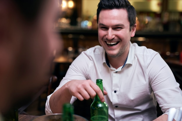 Homem alegre bebendo cerveja no bar