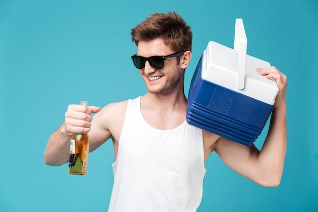 Homem alegre, bebendo cerveja. olhando de lado.