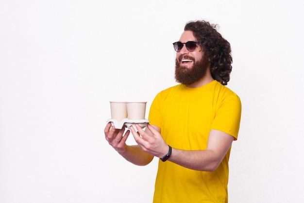 Homem alegre bonito hippie com cabelo comprido dando a alguém duas xícaras de café para viagem