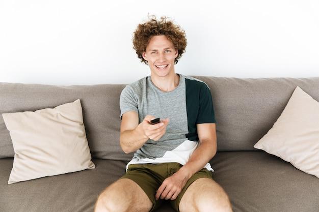 Homem alegre bonito sentado no sofá, segurando o controle remoto