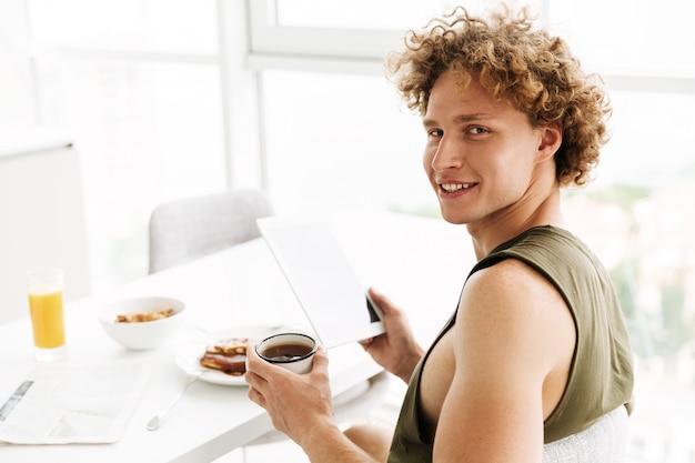 Homem alegre bonito usando computador tablet