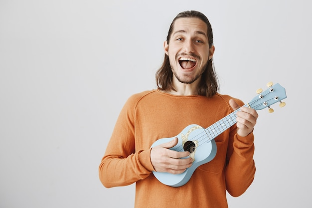 Homem alegre cantando e tocando cavaquinho com uma expressão feliz