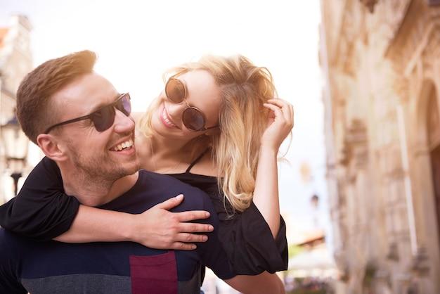 Homem alegre carregando sua namorada