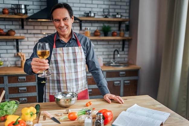Homem alegre carrinho na mesa na cozinha. ele segura um copo de vinho branco e sorri. pose de homem para a câmera. legumes coloridos e livro de receitas na mesa.