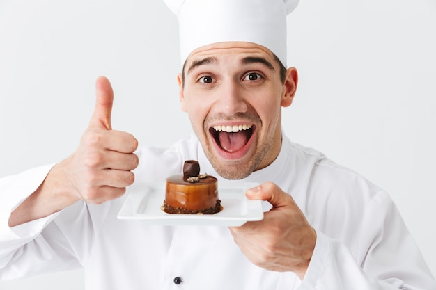 Homem alegre chef cozinheiro vestindo uniforme mostrando massa em um prato isolado sobre uma parede branca