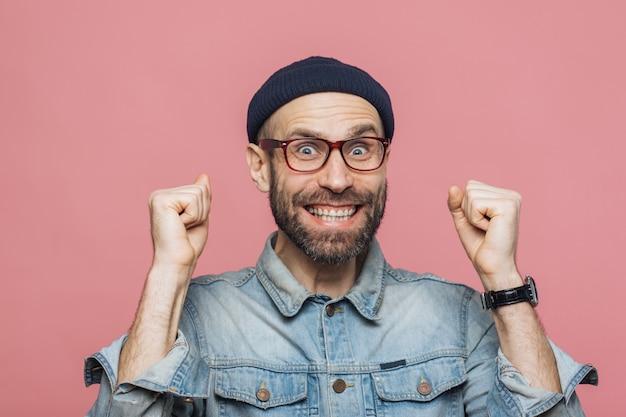 Homem alegre com barba grossa e bigode aperta os punhos e parece alegre, comemora sua vitória