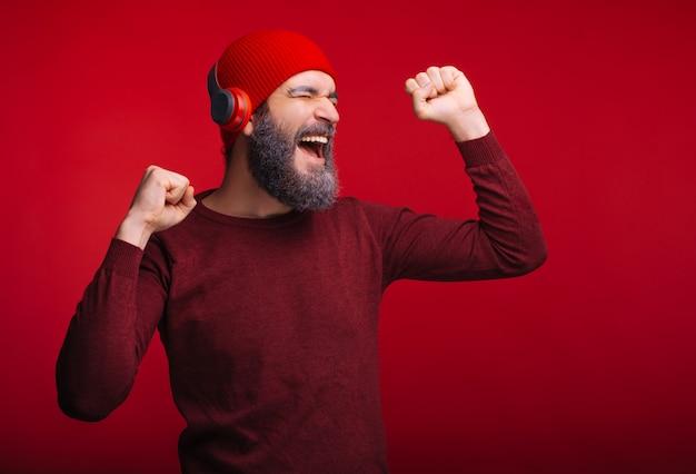 Homem alegre com barba ouvindo música em seus fones de ouvido sem fio