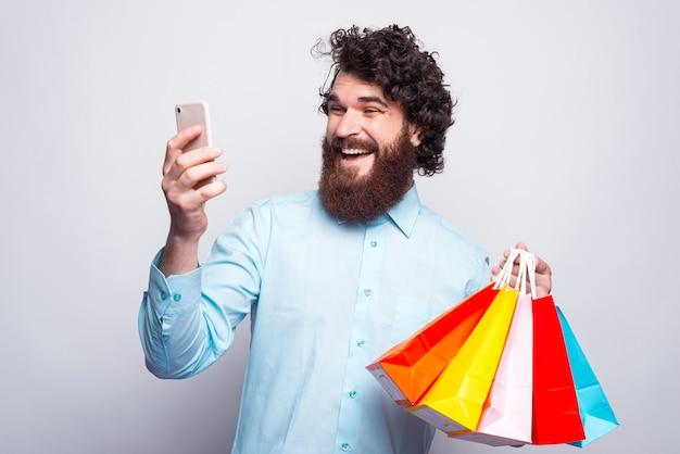 Homem alegre com barba, segurando sacolas de compras e olhando animado com o smartphone, pague online