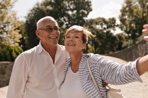 Homem alegre com bigode de óculos e camisa leve, sorrindo com uma mulher com cabelo curto em roupas azuis listradas no parque.