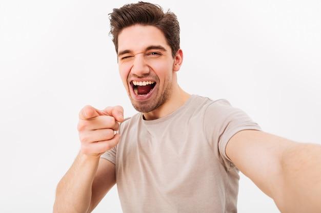 Homem alegre com cabelo castanho, gesticulando o dedo indicador na câmera, significando ei, enquanto você toma selfie, isolado sobre a parede branca