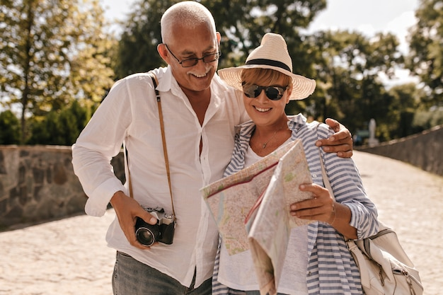 Homem alegre com cabelos grisalhos em camisa clara e jeans com câmera, sorrindo e olhando para o mapa com a senhora loira com chapéu e roupa azul no parque.