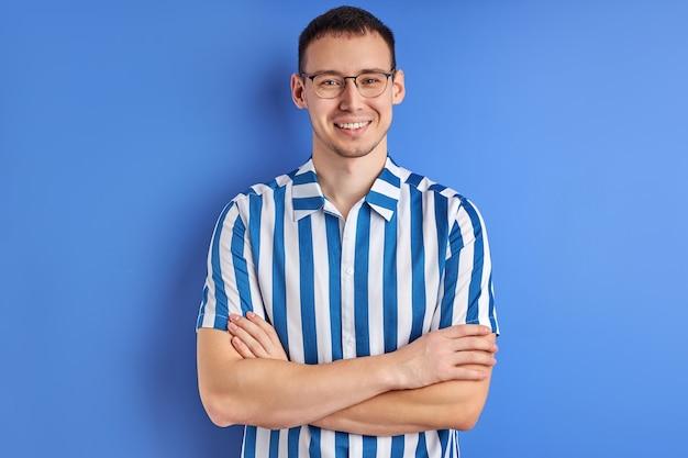 Homem alegre com camisa listrada e óculos, posando com os braços cruzados e sorrindo, isolado no fundo azul do estúdio