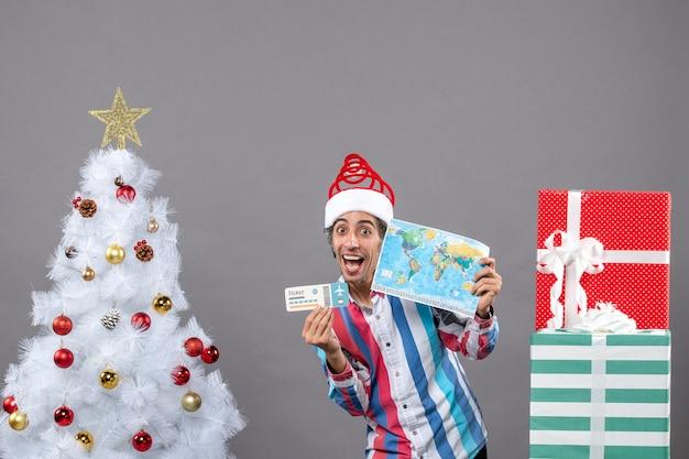 Homem alegre com chapéu de papai noel segurando mapa-múndi e bilhete de viagem