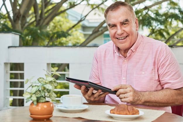 Homem alegre com computador tablet
