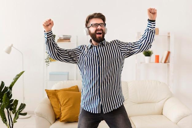 Homem alegre com fones de ouvido, curtindo música
