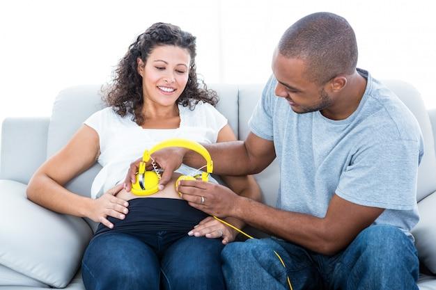 Homem alegre com fones de ouvido na barriga de grávida sentada no sofá em casa
