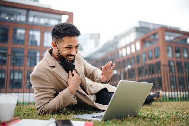 Homem alegre com laptop trabalhando ao ar livre no parque no conceito de cidade, coronavírus e videochamada.