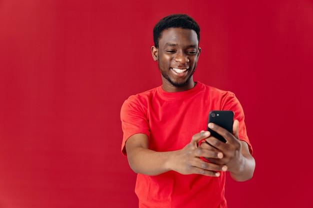 Homem alegre com o telefone nas mãos, vista cortada, comunicação de tecnologia de estúdio